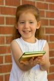 A menina oferece o livro Fotos de Stock Royalty Free