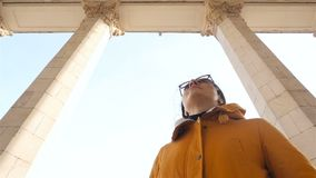 A menina olha as colunas altas Céu azul Movimento lento vídeos de arquivo