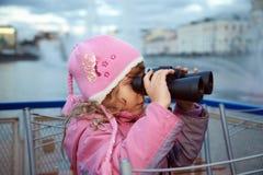 A menina olha através dos binóculos Imagens de Stock Royalty Free