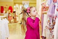 A menina olha com interesse em cima dos vestidos Foto de Stock Royalty Free