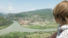 A menina olha do monastério ortodoxo georgian Jvari a Mtskheta na montanha video estoque