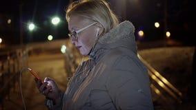A menina olha fixamente no telefone na rua na noite Anya est? vestindo os fones de ouvido brancos Uma brisa pequena est? fundindo filme