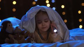 A menina olha imagens em um livro, ela guarda uma lanterna elétrica em sua mão Fundo de Bokeh vídeos de arquivo