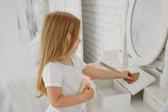 A menina olha no espelho Atrás da tabela do ` das senhoras Tabela de Bathroom fotos de stock