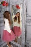 A menina olha no espelho em uma camiseta branca foto de stock