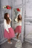 A menina olha no espelho em uma camiseta branca fotografia de stock