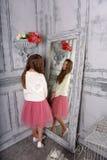 A menina olha no espelho em uma camiseta branca imagens de stock royalty free
