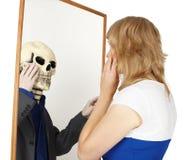 A menina olha no espelho falso Fotos de Stock Royalty Free