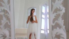A menina olha no espelho, toca no cabelo video estoque