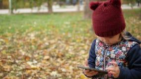 A menina olha no telefone no fundo das folhas amarelas outono filme