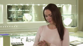A menina olha o anel em seu dedo na loja de joia video estoque