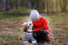 a menina olha o cachorrinho favorito fotografia de stock royalty free