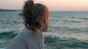 A menina olha o dia ventoso do mar no por do sol estilo de vida da concentração do pensamento do conceito vídeos de arquivo