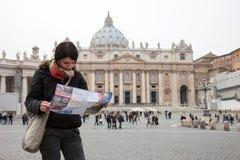A menina olha o mapa de Roma na praça San Pietro Foto de Stock