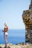 A menina olha o mar de um penhasco fotografia de stock royalty free