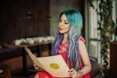 A menina olha o menu no café do vegetariano Fotografia de Stock