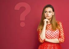 A menina olha o ponto de interrogação imagem de stock