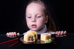 A menina olha os rolos em uma placa Foto de Stock Royalty Free