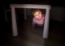 A menina olha para fora de debaixo da tabela Fotos de Stock Royalty Free