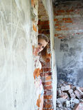 A menina olha para fora para das paredes Fotos de Stock Royalty Free