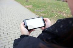 A menina olha seu smartphone que anda através do parque foto de stock