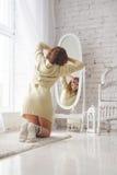 A menina olha si mesma no espelho Foto de Stock Royalty Free