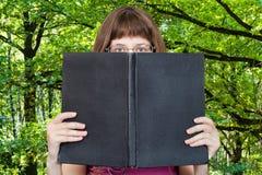 A menina olha sobre o livro grande e madeiras verdes Fotos de Stock Royalty Free