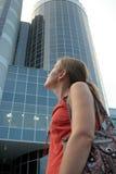 A menina olha um edifício elevado Imagens de Stock Royalty Free
