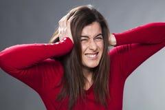 Menina olhando de sobrancelhas franzidas dos anos 30 que sofre da dor de cabeça que cobre suas orelhas com suas mãos Imagem de Stock