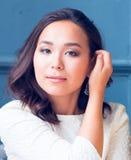 A menina oriental bonita endireita o cabelo fotos de stock royalty free