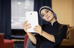 Menina oriental bonita na roupa muçulmana que fotografa-se em uma tabuleta eletrônica fotos de stock royalty free