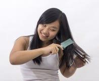 Menina oriental de sorriso que escova seu cabelo Imagem de Stock Royalty Free