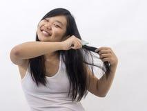 Menina oriental de sorriso que escova seu cabelo Imagens de Stock