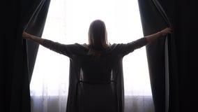 A menina ou a mulher abrem em casa cortinas pretas e olhar na janela vídeos de arquivo