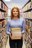 Menina ou mulher feliz do estudante com os livros na biblioteca Imagem de Stock Royalty Free