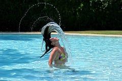 Menina ou mulher na piscina que joga o cabelo molhado para trás foto de stock
