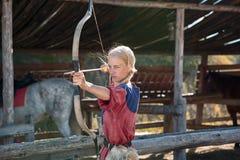 Menina ou tiro bonito da mulher, do arqueiro ou do caçador com curva e seta no dia ensolarado no alvo estável em pacotes de feno  fotos de stock