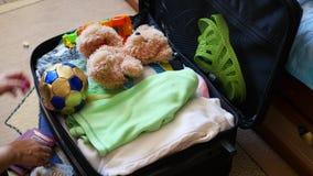 A menina põe coisas na mala de viagem para o curso no close up video estoque