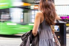 A menina põe a maca no escaninho enquanto o ônibus passa perto em Edimburgo fotos de stock