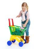 A menina põe o carrinho de compras Foto de Stock