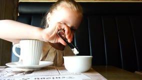 A menina põe partes dos tenazes de brasa do açúcar em um copo de chá da bebida quente vídeos de arquivo