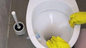 A menina põe sobre as luvas de borracha para lavar o toalete vídeos de arquivo