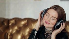 A menina põe sobre fones de ouvido e gerencie a música sobre vídeos de arquivo