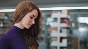 A menina põe um livro sobre a prateleira que está na biblioteca filme