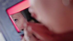 A menina põe uma fundação sobre sua cara A vista através do espelho que sustenta em suas mãos Plano agrad?vel mesmo cinematic vídeos de arquivo