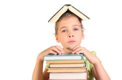 A menina põr as mãos sobre livros da pilha Imagem de Stock