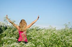 A menina pôs as mãos ao verão alto da grama da alcaravia do céu Imagens de Stock Royalty Free