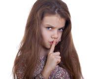 A menina pôs o dedo indicador aos bordos como o sinal do silêncio Foto de Stock Royalty Free