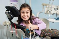 Menina paciente alegre que mostra os polegares acima no escritório dental da clínica Conceito da medicina, do stomatology e dos c fotografia de stock royalty free