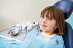 A menina paciente está esperando um exame na cadeira dental fotos de stock